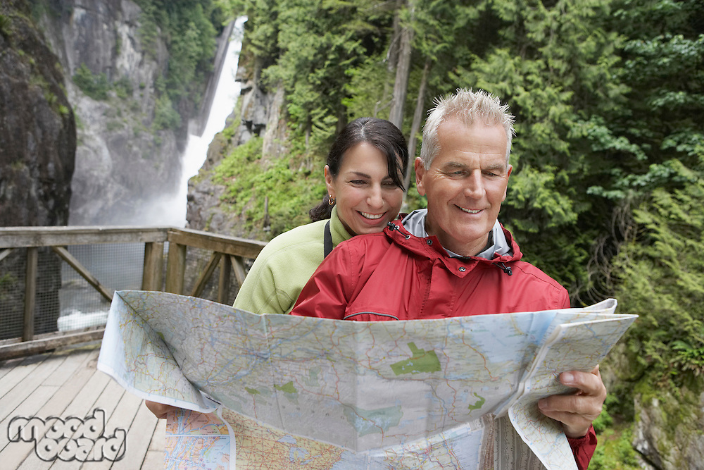 Man and woman reading map waterfall in background