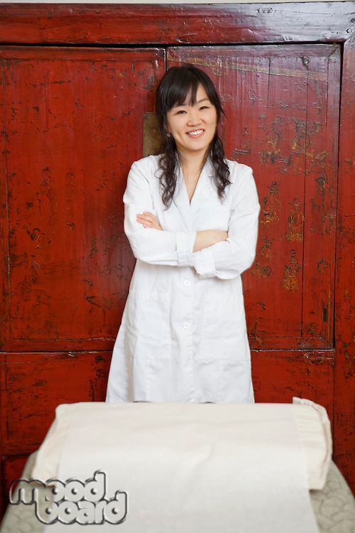 Portrait of a cheerful young Asian woman standing with bed in foreground
