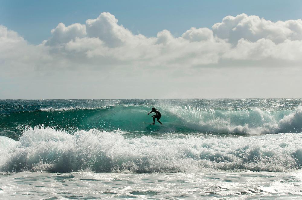 Surfing at Shipwreck Beach on Keoneloa Bay, Kauai, Hawaii