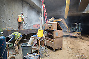 Workers use a jackhammer attachment on a mini excavator to remove excess concrete left over from slurry wall construction.