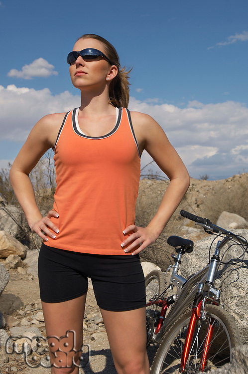 Female cyclist with hands on hips, in mountains