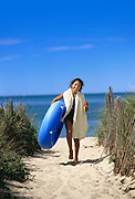Young girl with inner tube at beach entrance.