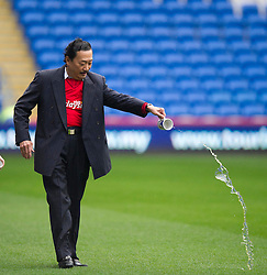 Cardiff City owner, Vincent Tan throws water on the pitch prior to kick off maybe a lucky charm for cardiff to win? - Photo mandatory by-line: Alex James/JMP - Mobile: 07966 386802 05/04/2014 - SPORT - FOOTBALL - Cardiff - Cardiff City Stadium - Cardiff City v Crystal Palace - Barclays Premier League