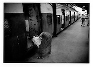 Woman loads a heavy sack of wood onto a commuter train in Mumbai's in Chhatrapati Shivaji Terminus (formerly known as Victoria Terminus).