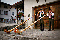 Photo of traditionally dressed Swiss men playing Alphorns in Gruyeres, Switzerland