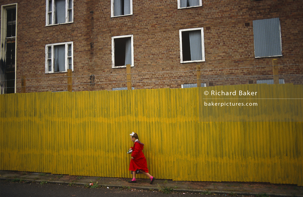 A young girl dressed in a red coat and pink socks walks half-way along a bright yellow stretch of corrugated sheet metal that screens off a derelict block of flats in Toxteth, Liverpool, England. The flats' windows are also partly-boarded up in an area that saw serious rioting in 1981.  Toxteth is an inner-city area of Liverpool, Merseyside. It is located to the south of the city and is synonymous with social issues, degradation and poverty with some of the most underprivileged families in the UK. Recently many streets in the worst areas have been demolished  including Beatle Ringo Starr's childhood home.