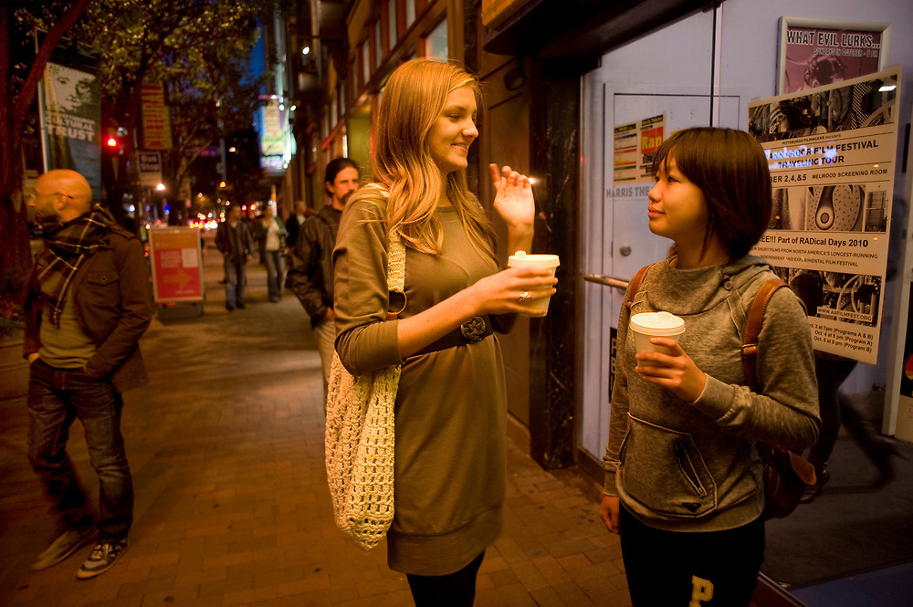 University of Pittsburgh students Hannah Masters (left) and Liwen Zhang (right) discuss in front of the Harris Theater which gallery to visit next during the Pittsburgh Cultural Trust Fall Gallery Crawl in downtown Pittsburgh