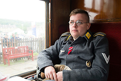 A reenactor potraying a German Paratrooper (Fallschirmjäger) in walking out uniform travels on a train during the East Lancashire Railway 1940's Weekend. He wears the rank of Obergefreiter on his left sleeve. The medal ribbons for the Iron Cross second class (EK2) and Eastern Front Medal (Ostmedaille) on the front of his fight jacket (Fliegerbluse) and the Paratrooper badge (Fallschirmspringerabzeichen) on the left front. <br />