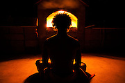 Illuminated by a roaring fire, a yogi meditates during a retreat near Lake Arrowhead, California.