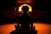 Illuminated by a roaring fire, a yogi meditates during a retreat near Lake Arrowhead, California.
