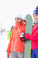 Beautiful young women with snowboard looking away