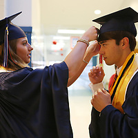 Baldwyn High School senior co-valedictorian Ingrid Osmundson, left, helps her classmate Tyler Raines fix his cap before the start of Friday night's graduation ceremony at the school.