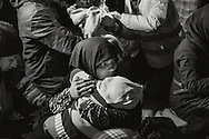 A migrant woman warms her child after a night crossing of the Aegean Sea. Lesbos, March 20, 2016.