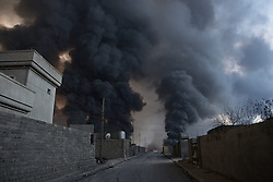 Licensed to London News Pictures. 20/10/2016. A cloud of smoke, rising from burning oil wells that have been alight for around two months, is seen towering over houses in the town of Qayyarah, Iraq. The oil wells, located in a neighbourhood on the edge of the town, were set alight in July by retreating Islamic State militants as part of a scorched earth policy.<br /> <br /> Since being retaken from the Islamic State the town of Qayyarah has become an important staging post for the Iraqi Army, and some US support elements, in the buildup to the Mosul offensive. Photo credit: Matt Cetti-Roberts/LNP