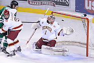 Michael Parks (15), senior forward for North Dakota, makes his way past Joey LaLeggia (21) to score on Sam Brittain (1) of Denver University on a January 24, 2014 at Magness Arena in Denver, Colorado.