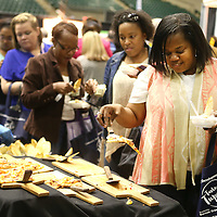 Adam Robison | BUY AT PHOTOS.DJOURNAL.COM<br /> Natasha Thomas, of Tupelo, gets a slice of pizza from the Old Venice Pizza Co. booth during The Taste of Tupelo Thursday night at the BancorpSouth Arena in Tupelo.