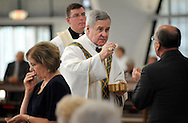 The Most Rev. Robert J. Carlson serves Communion during a Mass of Ordination to the Diaconate where Brother Francis Hein, OSB, and Brother Cassian Koenemann, OSB, became transitional Deacons at the Church of the Abbey of Saint Mary and Saint Louis in Creve Coeur, Mo. Saturday, Aug. 11, 2012. Photo © copyright 2012 Sid Hastings.