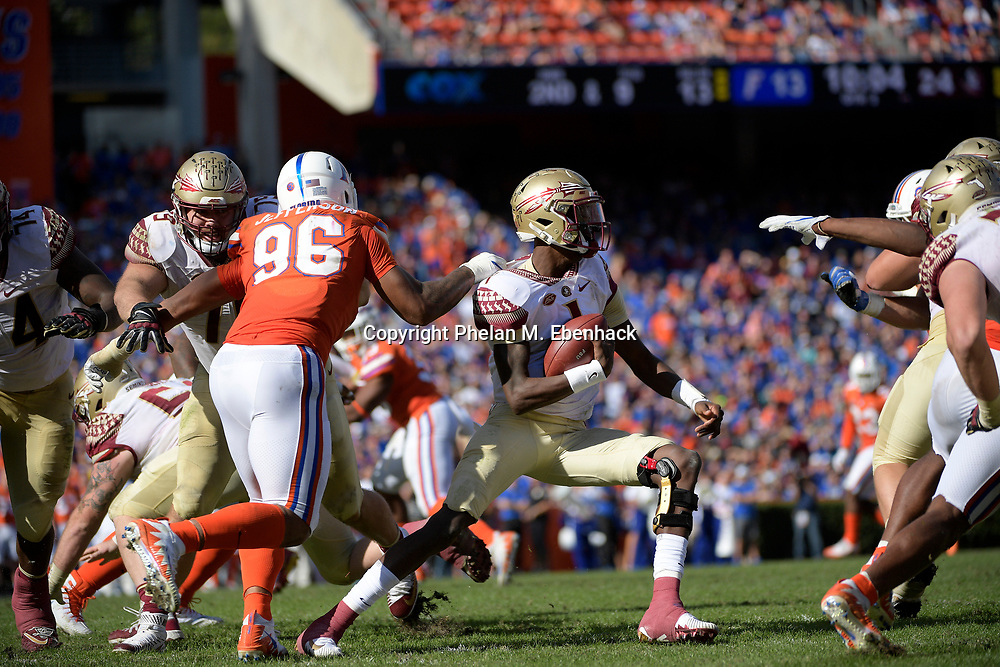 Florida defensive lineman Cece Jefferson (96) grabs the jersey of Florida State quarterback James Blackman (1) during the second half of an NCAA college football game Saturday, Nov. 25, 2017, in Gainesville, Fla. FSU won 38-22. (Photo by Phelan M. Ebenhack)