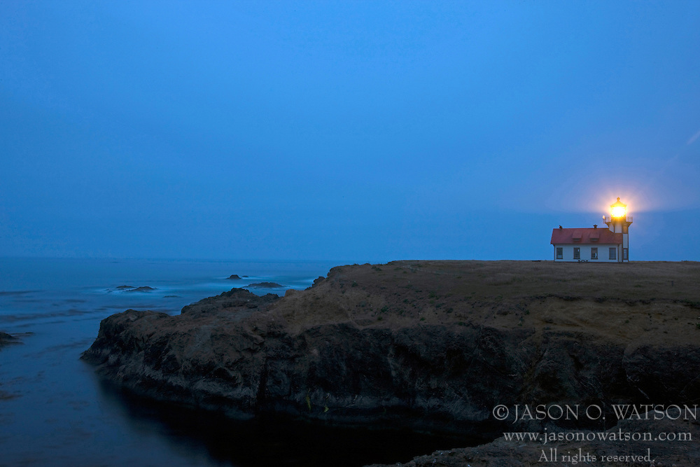The Point Cabrillo lighthouse stands as a beacon at dusk along Mendocino cliffs near Mendocino, California, USA.