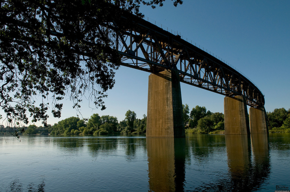 A train bridge crosses the Sacramento River in Caldwell Park in Redding, California. ..The Sacramento River, California's largest river flowing 375 miles, from Mount Shasta in the north through the Central Valley and the Delta to San Francisco Bay, this river constitutes an irreplaceable resource to Northern California's ecology...Boating, fishing, camping and swimming on the Sacramento and its reservoirs attract more than 8 million visitors a year. ..The 21-mile stretch from Redding to Balls Ferry is perfect for scenic touring and shorter trips. For the adventuresome, the breath-taking 33-mile stretch between Balls Ferry and Red Bluff is your ticket..