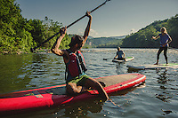 Men and women paddle boarding and camping on the New river in Virginia, in the heart of the Blue Ridge Mountains.