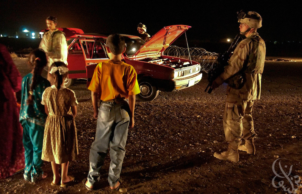 Iraqi children watch as Delta company, 3-507 U.S. Army 101st Airborne Specialist William Nickels(r) from Fayetteville, Arkansas and his unit  search their car for weapons during a night vehicle checkpoint July 25, 2003 in Mosul, Iraq.