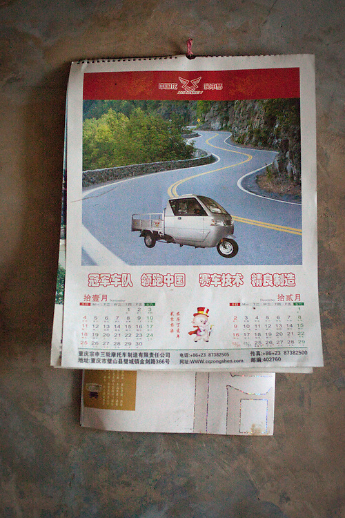 A calendar, given to Wei Xinyuan as a present by the company that sold him his tuk-tuk hangs on the wall of his living room. This vehicle was going to be used to haul the heavy bags of rice and corn harvested from the fields. It was going to be used by their youngest son so he could make a little cash by driving people to the market. <br /> <br /> Late one night, the tuk-tuk was stolen. The thieves barricaded the door from the outside and drove away as the family, hearing the sound of the engine, was helpless to stop them. Soon after, Wei and Lu&rsquo;s youngest son, seeing no opportunity for cash income in the village, joined his brother in the city.