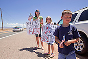 04 AUGUST 2010 -- GILBERT, AZ: L to R background to foreground: Holli Pearce (CQ Holli)  her daughter Emalyn Pearce (CQ) 8, and son Nathen Pearce (CQ NATHEN) from Mesa, put their hands over their hearts as the Det. Carlos Ledesma's cortege passes at the funeral for Chandler police detective Carlos Ledesma Wednesday. Kenzlie is the daughter of fallen Phoenix Police Officer Shane Figueroa. Ledesma was killed during a shoot out with suspected drug dealers during an undercover operation in south Phoenix Wednesday July 28.   PHOTO BY JACK KURTZ
