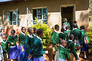 The pupils of Endagikot school rush to their training session by the ICS Raleigh SWASH (school water, sanitation and hygiene plan) project. Mbulu, Manyara district, Tanzania. Working in partnership with the Diocese of Mbulu Development Department (DMDD); part of Caritas Tanzania.