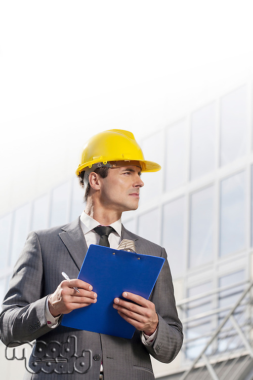 Young male architect with clipboard looking away in front of office building