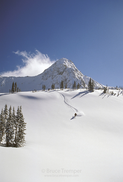 Backcountry skier, Bob Greely skiing powder in front of the Pfeifferhorn, Little Cottonwood Canyon, Utah.