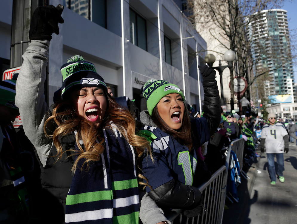 Western Washington University students Teena Thach (L), 21, and Shawna Mori, 20, stand along 4th Avenue in downtown at the Super Bowl victory parade for the Seattle Seahawks in Seattle, Washington February 5, 2014.  REUTERS/Jason Redmond  (UNITED STATES)