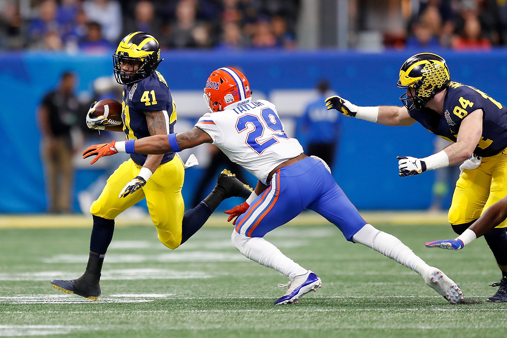 Michigan Wolverines running back Christian Turner #41 runs the ball past Florida Gators defensive back Jeawon Taylor #29 during the Chick-fil-A Peach Bowl, Saturday, December 29, 2018, in Atlanta. ( Paul Abell via Abell Images for Chick-fil-A Peach Bowl)