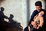 Munem Adnan Abdullah, 37, is holding Mohammed, 4, (right) one of his two disabled children, in Fallujah, Iraq. Ayob, 5, his second disabled child is being pushed by one of his two older, and healthy brothers, both born before the two 2004 battles. The parents and their relatives have no history of birth defects.