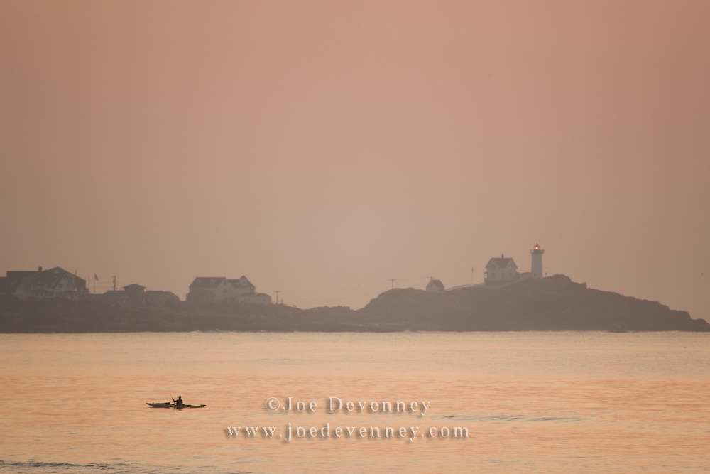 Kayaker at sunrise. Cape Neddick Lighthouse. York Beach, Maine