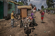 """Daily life on the main street in """"Jamaica"""" the Rastafarian district of Shashemene.  It is moving day for these young Oromo men, as a well dressed young woman carries firewood home.  The Rastas are now vastly outnumbered by local Oromo people who warmly receive outsiders.  Shashemene, Ethiopia."""