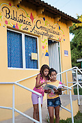 Giovana (right) and Zilá (left) outside the front of the community library, Biblioteca Comunitaria do Arquipelago, Porte Alegre, Brazil. <br /> <br /> Prior to its complition this library was a run down shed and it's now full of books and has lots of colourful cushions on the floor . There is art and craft hanging from the walls and the celing.<br /> <br /> Cirandar is working in partnership with  C&A and C&A Instituto to implement a network of Community Libraries in eight communities of Porto Alegre.