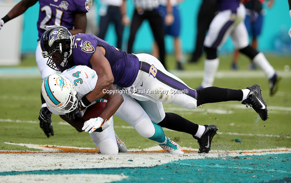 Baltimore Ravens inside linebacker Daryl Smith (51) tackles Miami Dolphins running back Damien Williams (34) on a first quarter pass reception good for a 5 yard gain during the 2015 week 13 regular season NFL football game against the Miami Dolphins on Sunday, Dec. 6, 2015 in Miami Gardens, Fla. The Dolphins won the game 15-13. (©Paul Anthony Spinelli)