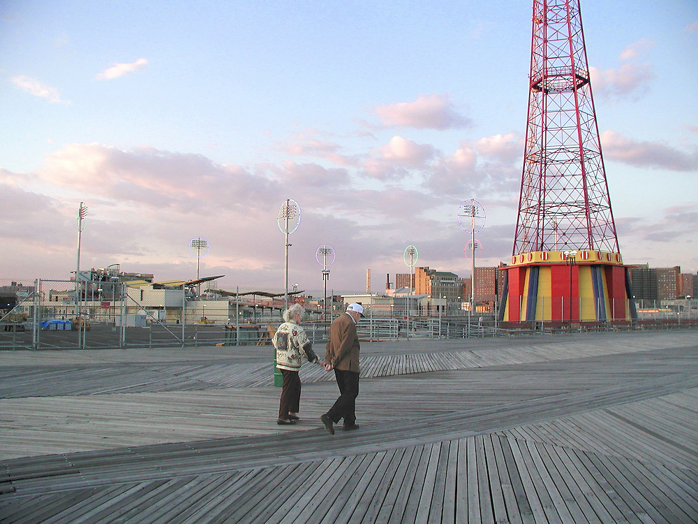 """A couple strolls along the boardwalk near the old """"Parachute Jump"""" ride and with construction then going on for the new """"Brooklyn Cyclones"""" ball park in the background."""