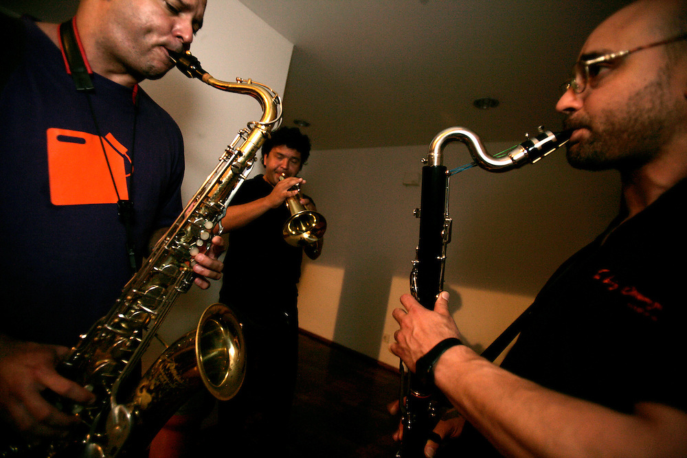 "Three members of ""Jazz ao Centro Orchestra"" practising before an orchestra rehearsal."