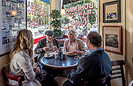 Inside Mario's Bohemian Cigar Store Cafe in North Beach, San Francisco. People visit at the corner table in the small cafe while eating breakfast.