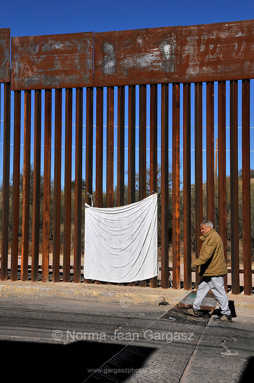 A white sheet covered with memorial messages marks the location on the border wall in Nogales, Sonora, Mexico, where a 16-year-old who was allegedly throwing rocks across the border at a US Border Patrol agent in Nogales, Arizona, USA, was shot and killed by the agent in October of 2012.  A missing grate from a binational drainge tunnel enables people in Mexico to cross underground illegally in to Arizona, USA,