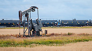 A pumpjack pumps oil from a shale oil well outside Williston, a section of the Bakken oil field. In the background, a freight train with tank cars full of oil.
