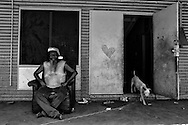 Ralph sitting in front of family home on Christmas morning, in One Mile Community.<br />