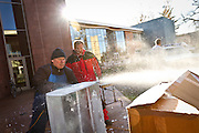 Ice sculptor Bill Gordish, left, flattens a block of ice into a clean 90° angle before stacking and carving an 8' tall beverage luge for the Fire and Ice Dinner in the Dining Hall.