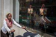 A lady pushes a double child's buggy passes the luxury shop window of Louis Vuitton featuring their exclusive range of bags with the face of Leonardo da Vinci's Mona Lisa - a collaboration with the artist Jeff Koons and part of work entitled The Masters Collection, on 5th July 2017, on New Bond Street, in London England.
