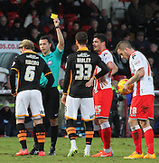 Referee Dean Whitestone shows Christian Ribeiro a yellow card during the Sky Bet League 2 match between Stevenage and Exeter City at the Lamex Stadium, Stevenage, England on 20 December 2014. Photo by Kieran Clarke.