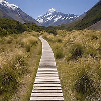 New Zealand, South Island, Aoraki Mount Cook National Park, Mount Cook looms above wooden boardwalks along Hooker Valley hiking trail in Southern Alps on clear summer afternoon