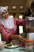 Iin Hartini using the blender in her kitchen.<br /> <br /> In 2007 Iin started her own business selling Nasi Goreng (fried rice). <br /> <br /> She makes it in bulk for the school canteen to sell to children who have their breakfast at school. <br /> <br /> Prior to signing up to Usaha Wanita Iin had been beginning to feel demotivated about her work and for a short time ceased making the rice. Since receiving the advice and mentoring she has become reenergised for her business and her profits have tripled.