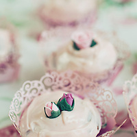 A collection of pink and white cupcakes with roses ontop